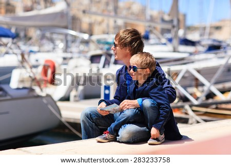 father and little son looking at map in the port of Malta - stock photo