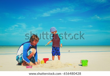 father and little son play with sand on beach