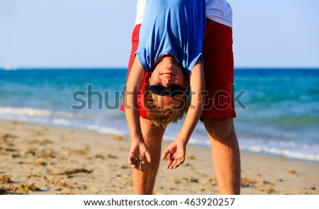 father and little son playing on beach