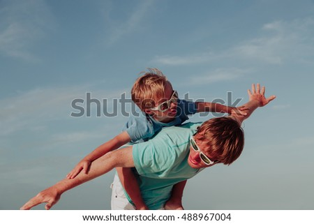 Father and little son playing on sky