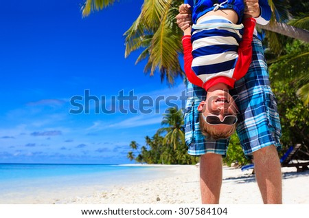 father and little son playing on summer beach, family vacation fun - stock photo