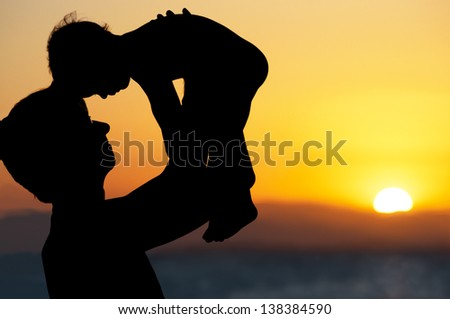 Father and little son - silhouettes on beach at sunset - stock photo
