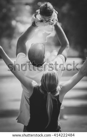 Father and mother are celebrating with their son. Happy interracial family is enjoying a day in the park. Little mulatto baby girl and boy. Successful adoption. Diverse family. - stock photo