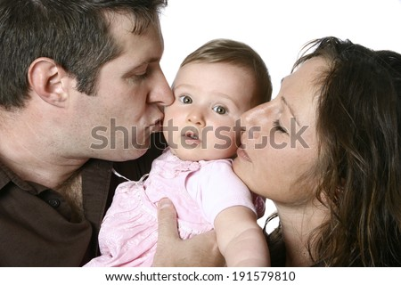 Father and mother kissing baby girl - stock photo