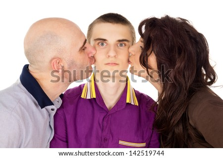 Father and mother kissing son cheek - stock photo