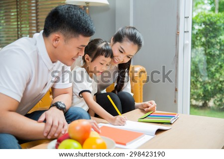Father and mother Teaching children to do their homework at home - stock photo
