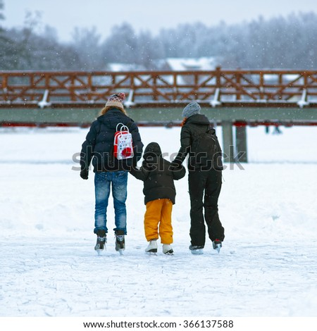 Father and mother teaching kid to skate in the rink in winter. Skating involves any sports or recreational activity which consists of traveling on surfaces or on ice using skates. - stock photo