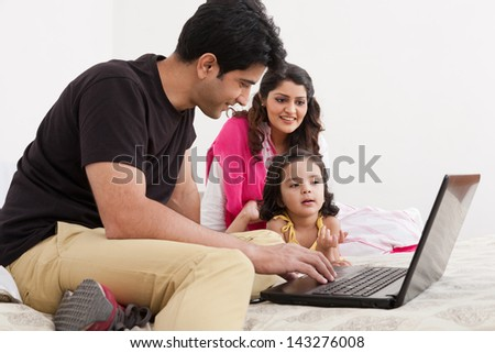 father and mother using laptop with daughter, Muslim family of three. - stock photo