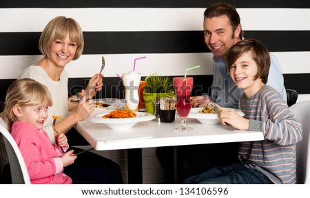 Father and mother with children enjoying meal in restaurant.