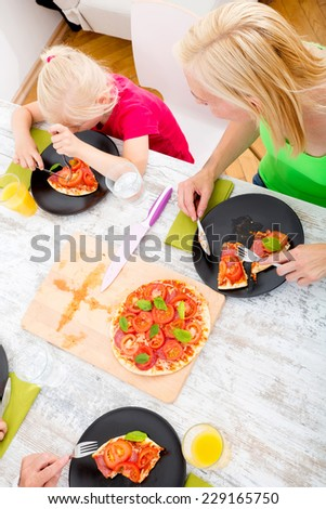 Father and mother with son and daughter eating Pizza for lunch or dinner.