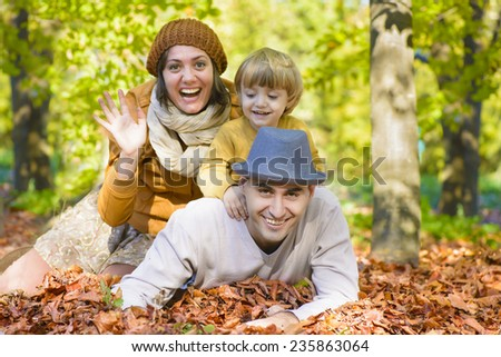 Father and Mother with their kid in forest, autumn time - stock photo