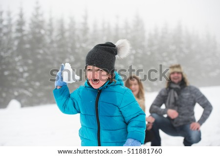 Father and mother with their son, playing in the snow.
