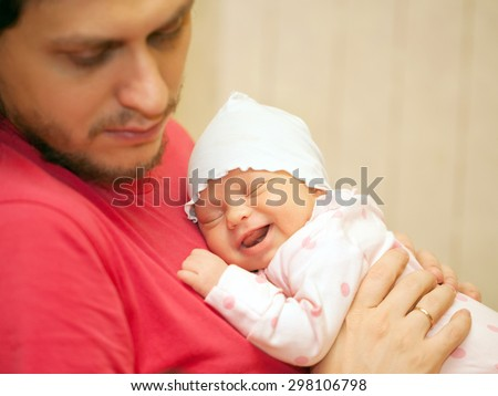Father and newborn baby. The smiling kid sleeping on father's chest. Family ties. Selective focus on the face of the baby.