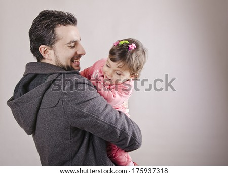 father and one year daughter isolated on gray background - stock photo