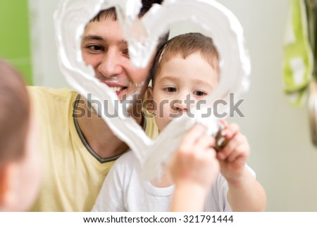 Father and preschooler son draw heart shape on mirror with shaving foam playing in bathroom - stock photo