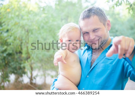 Father and small daughter laughing and bonding. Happy father holds the little daughter in his arms among the trees, fatherhood, happy, family, walk