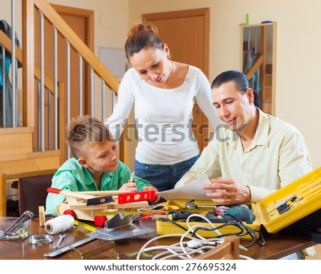 Father and son are doing with their hands crafts in home