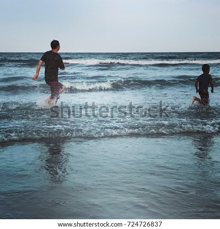 Father and son are running in the sea water happy in Huahin Thailand in sunny day , 25 nov 2017