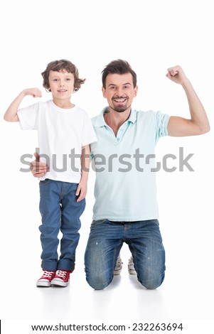 Father and son are showing biceps and smiling on white background. - stock photo