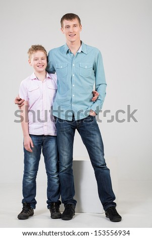 Father and son are standing in an embrace in jeans and shirts - stock photo