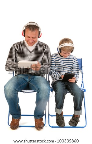 Father and son are together gaming with tablet PC - stock photo