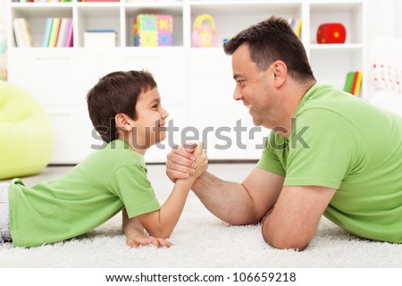 Father and son arm wrestling at home - childhood and parenting - stock photo