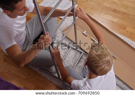 Father And Son Assembling Furniture . Boy Helping His Dad With Building  Work At Home.