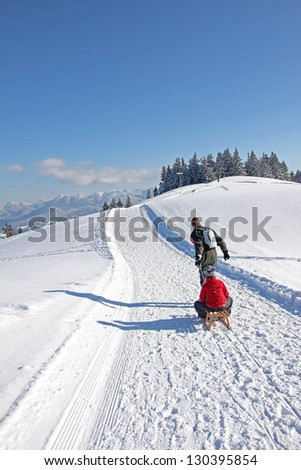 father and son at a coasting slide in the bavarian alps, enjoying winter activity - stock photo