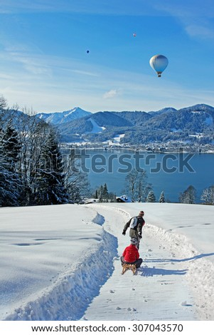 father and son at a tobogganing route in the bavarian alps, view to lake tegernsee, hot air balloons - stock photo