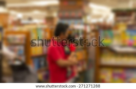 Father and son at book shop in defocused blur concept. - stock photo