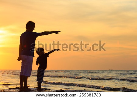 father and son at sunset beach, pointing at the sun - stock photo