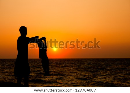 father and son at sunset sea closeup