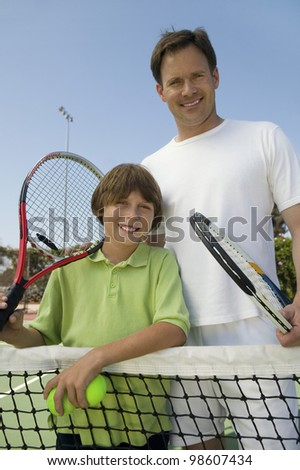 Father and Son at Tennis Net - stock photo