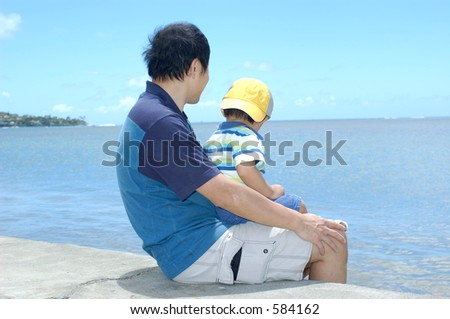 father and son at the beach - stock photo