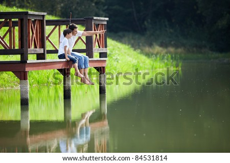 Father and son at the lake - stock photo