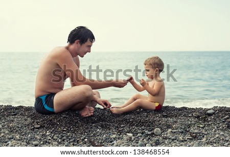 Father and son at the sea beach - stock photo