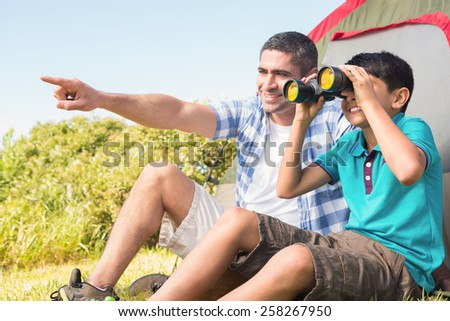 Father and son beside their tent in the countryside on a sunny day - stock photo