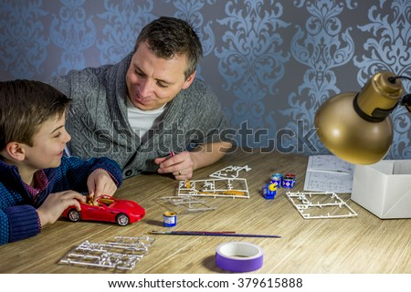 father and son building a model car
