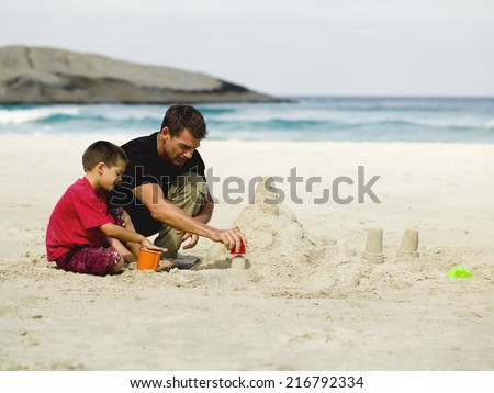 Father and son building sand castles on the beach. - stock photo