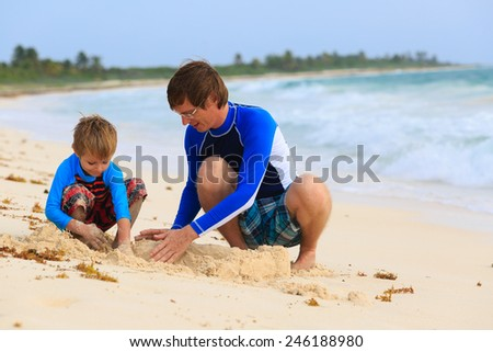 father and son building sandcastle on summer beach