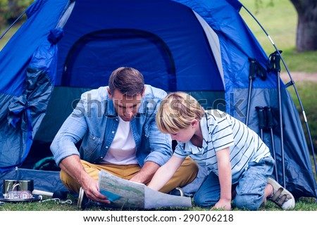 Father and son camping in the park on a sunny day - stock photo