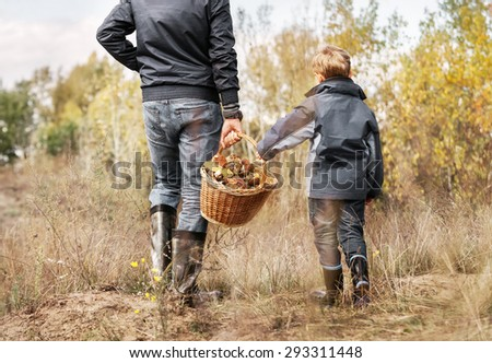 Father and son carry full basket of mushrooms - stock photo
