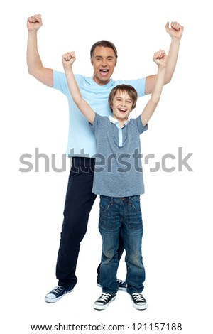 Father and son celebrating their success. Rejoicing with raised arms. - stock photo