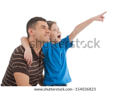 Father and son. Cheerful father and son standing close to each other while child pointing away