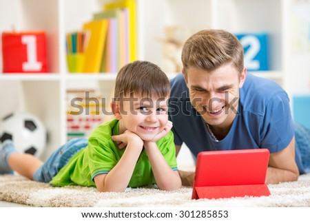 Father and son child playing with digital tablet
