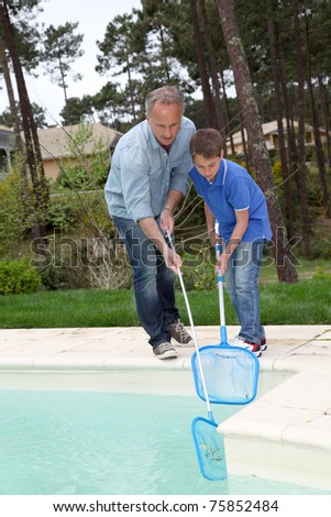 Father and son cleaning swimming-pool