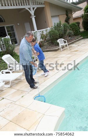 Father and son cleaning swimming-pool - stock photo