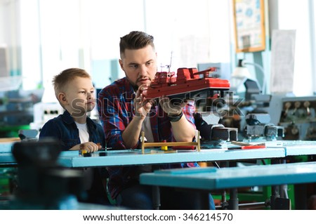 Father and son collect ship model - stock photo