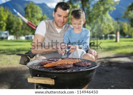 Father and son cooking in camp