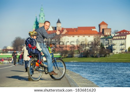 Father and son cycling in city. - stock photo
